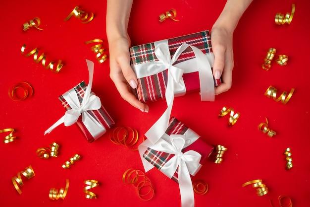 Femininas mãos segurando presente em um vermelho