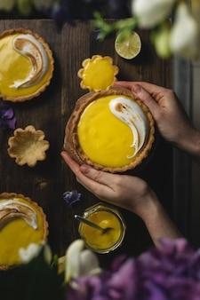 Femininas mãos segurando torta de limão merengue na mesa rústica escura