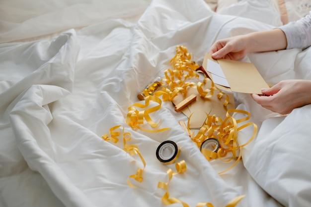 Femininas mãos segurando um cartão de presente, envelope e caixa de presente sobre o cobertor da cama. ano novo e o conceito de natal. vista horizontal superior