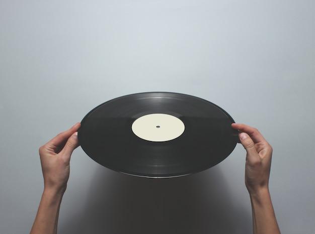 Femininas mãos segurando um disco de vinil retrô sobre uma mesa cinza. vista superior, minimalismo.