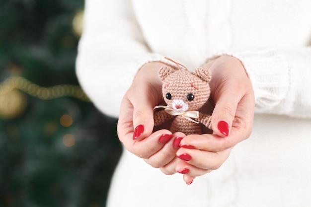 Femininas mãos segurando um fofo urso feliz