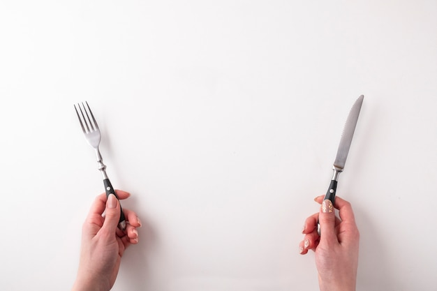Femininas mãos segurando um garfo e faca em branco