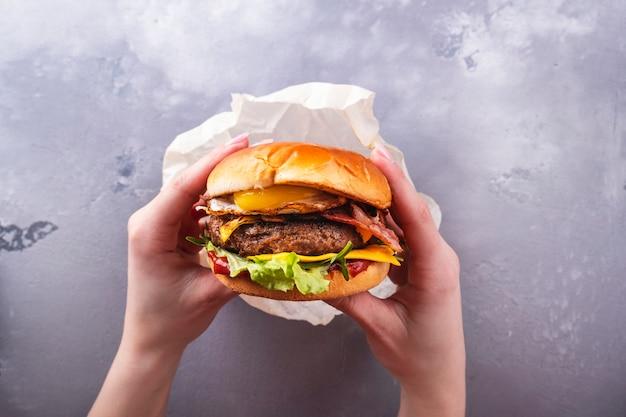 Femininas mãos segurando um ovo frito de hambúrguer saboroso. t