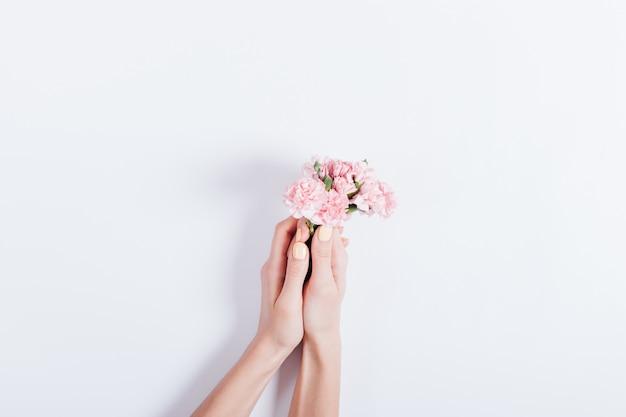 Femininas mãos segurando um pequeno buquê de flores cor de rosa