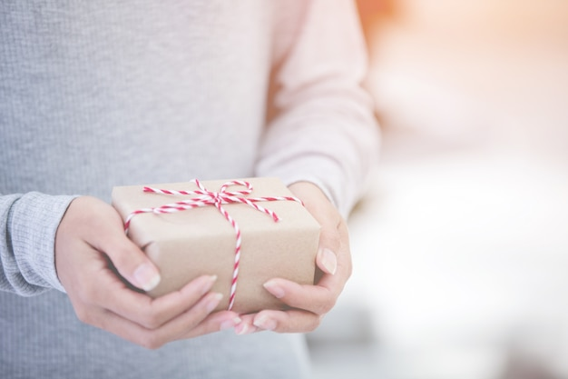 Femininas mãos segurando um pequeno presente. pequeno presente nas mãos.