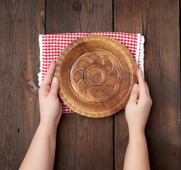 Femininas mãos segurando um prato redondo de madeira vazio