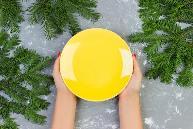 Femininas mãos segurando um prato vazio amarelo