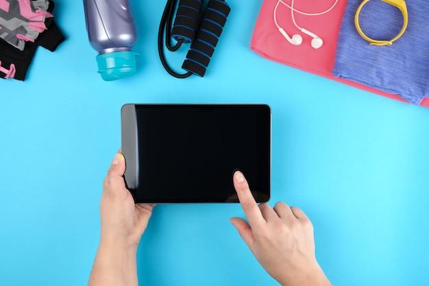 Femininas mãos segurando um tablet eletrônico com uma tela preta em branco, ao lado dele é roupas de fitness