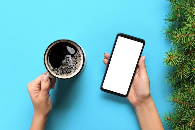 Femininas mãos segurando um telefone móvel preto com tela branca em branco e caneca de café