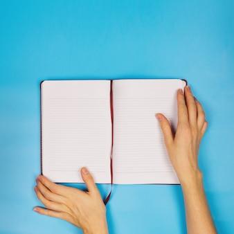 Femininas mãos segurando uma agenda vazia no fundo azul