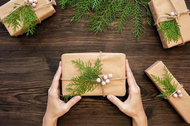 Femininas mãos segurando uma caixa de presente de natal em madeira escura