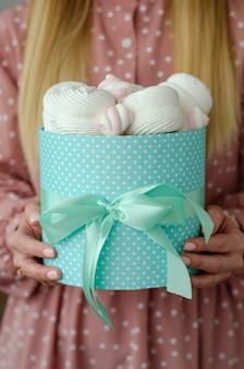 Femininas mãos segurando uma caixa grande turquesa com fita cheia de marshmallows e merengues.