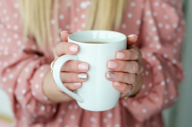 Femininas mãos segurando uma caneca branca com bebida. fechar-se. fundo desfocado