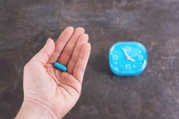 Femininas mãos segurando uma cápsula.