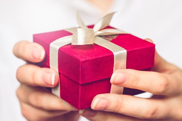 Femininas mãos segurando uma pequena caixa vermelha com um presente.