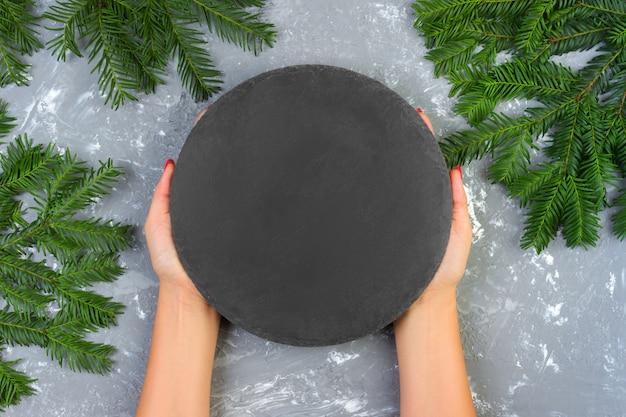 Femininas mãos segurando uma placa de pedra ardósia preta vazia com galhos de natal. vista de cima