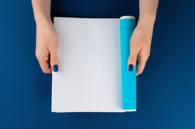 Femininas mãos segurando uma revista em branco com espaço de cópia, vista superior
