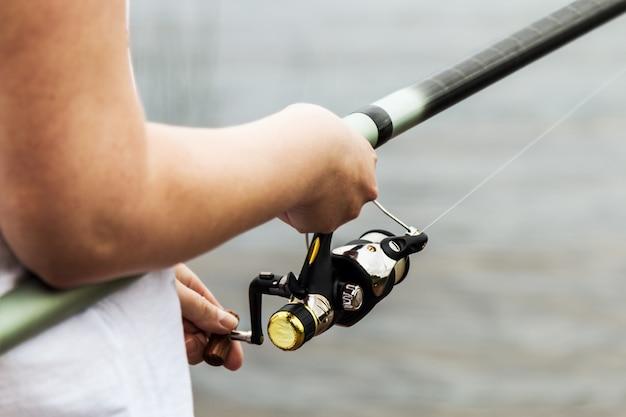 Femininas mãos segurando uma vara de pescar