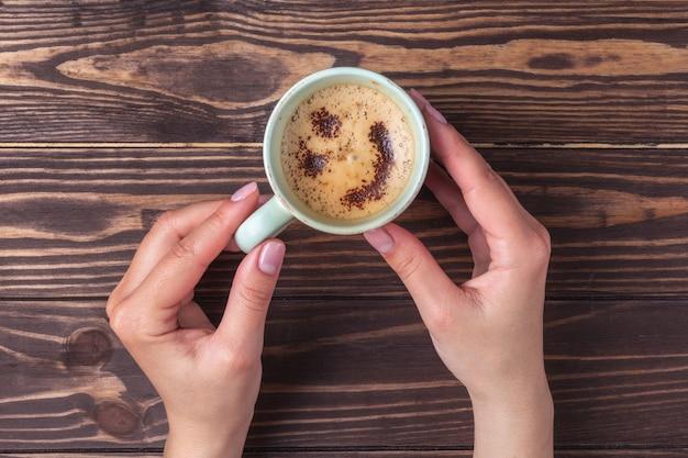 Femininas mãos segurando uma xícara de café com espuma sobre uma mesa de madeira, vista superior. café com leite ou cappuccino com chocolate granulado.