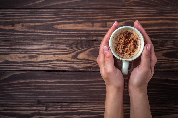 Femininas mãos segurando uma xícara de café com espuma sobre uma mesa de madeira, vista superior.