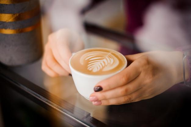 Femininas mãos segurando uma xícara de café com leite com arte fora da janela