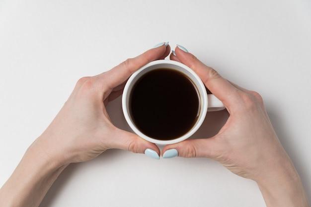 Femininas mãos segurando uma xícara de café forte. café da manhã.