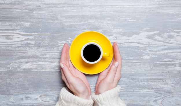 Femininas mãos segurando uma xícara de café.