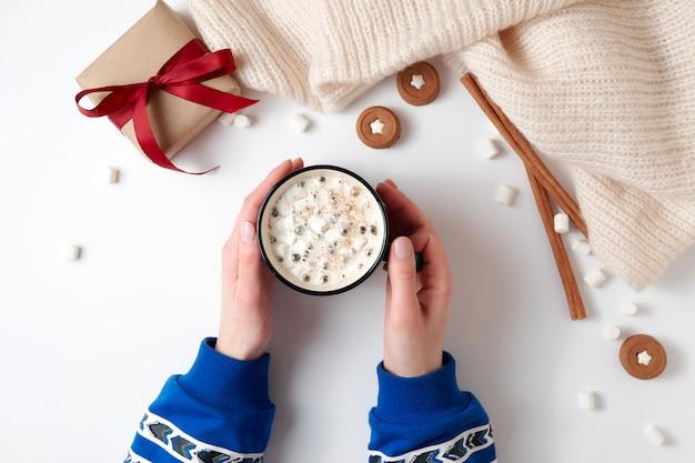 Femininas mãos segurando uma xícara de chocolate quente com marshmallow