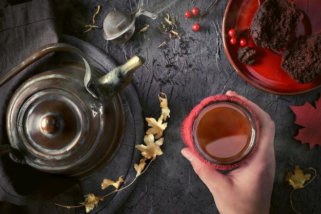 Femininas mãos segurando uma xícara quente de chá em uma manhã fria no outono com folhas de outono