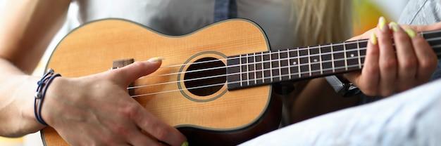 Femininas mãos segurando violão ukulele aprendendo a tocar