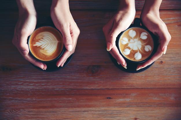 Femininas mãos segurando xícaras de café no fundo da mesa de madeira rústica