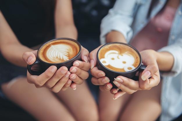 Femininas mãos segurando xícaras de café.