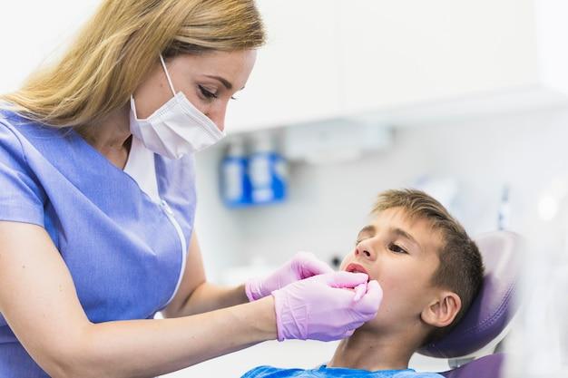 Femininas, odontólogo, examinando, criança, paciente, dentes, em, clínica