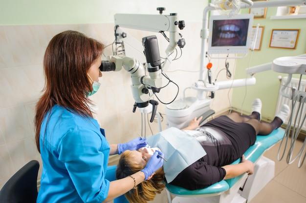 Femininas, odontólogo, trabalhando, com, microscópio, em, modernos, odontólogo, clínica