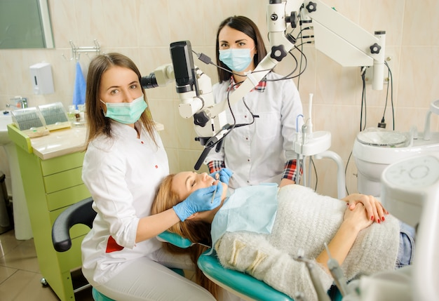 Femininas, odontólogo, tratando cárie, usando, microscópio, em, a, dentista, escritório