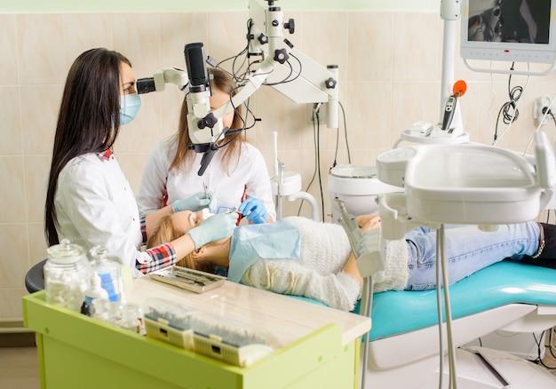 Femininas, odontólogo, tratando cárie, usando, microscópio, em, a, odontólogo, escritório