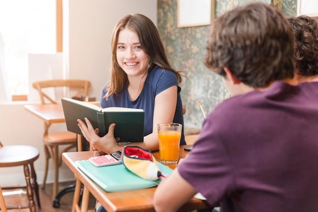 Feminino adolescente lendo livro no café perto de amigos