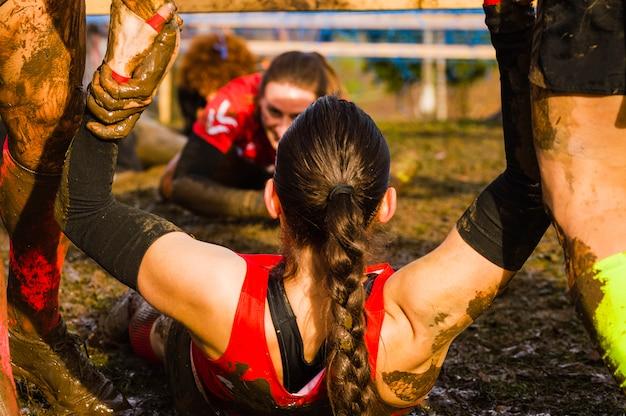 Feminino ajudado por uma mão amiga em uma corrida de lama xtreme