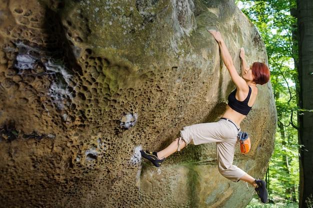 Feminino alpinista em seu caminho desafiador, bouldering