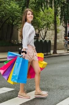 Feminino andando com sacolas de compras