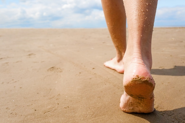 Feminino, andando pela praia.