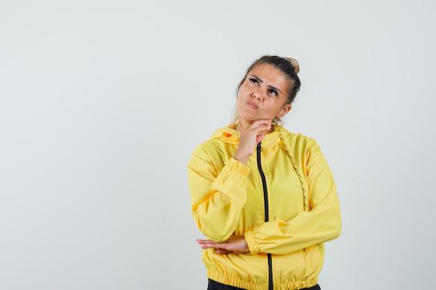 Feminino apoiando o queixo na mão em traje esporte e parecendo pensativo. vista frontal.
