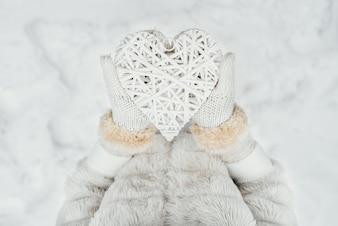 Feminino as mãos em luvas brancas de malha com um coração branco romântico vintage entrelaçado
