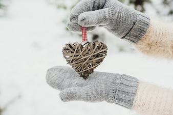 Feminino as mãos em luvas de malha com um coração romântico vintage entrelaçado