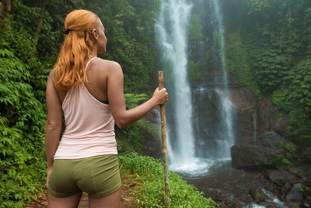 Feminino aventureiro olhando cachoeira