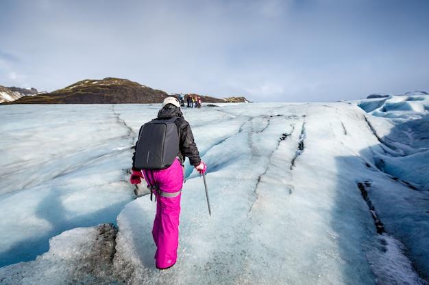 Feminino caminhante andando na geleira em solheimajokull