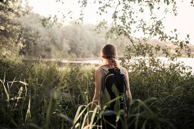 Feminino caminhante andando na grama verde perto do lago