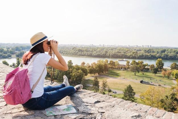 Feminino caminhante olhando a vista através de binóculos
