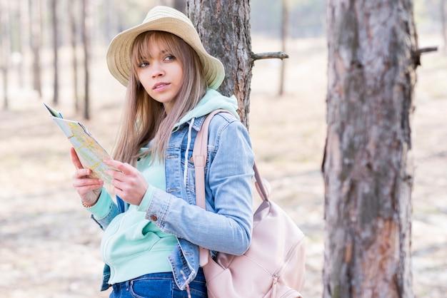 Feminino caminhante segurando o mapa na mão, olhando para longe