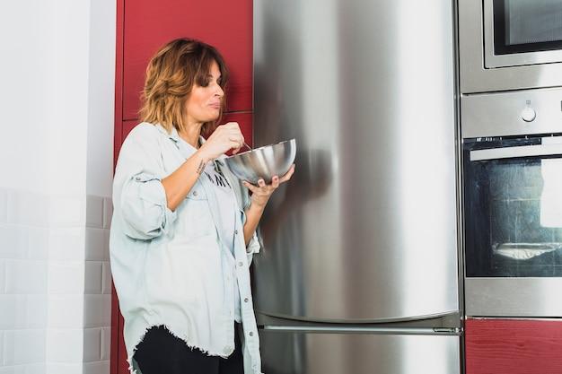 Feminino comendo em pé perto de aparelhos de cozinha